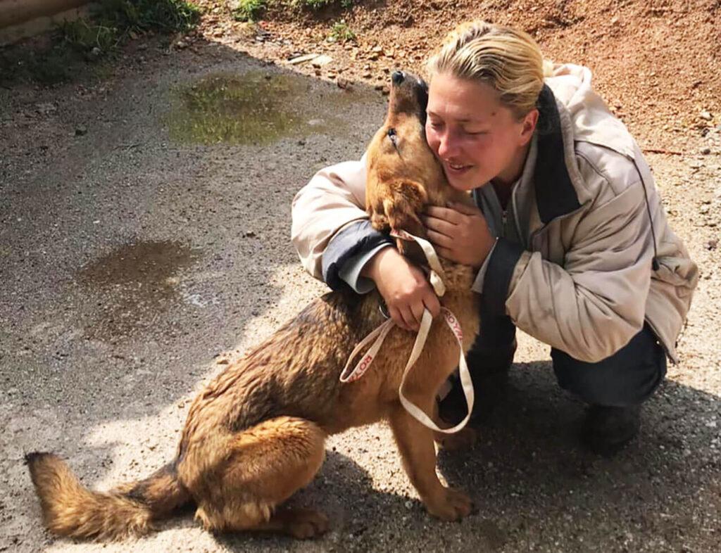 Naida hugging her rescued dog